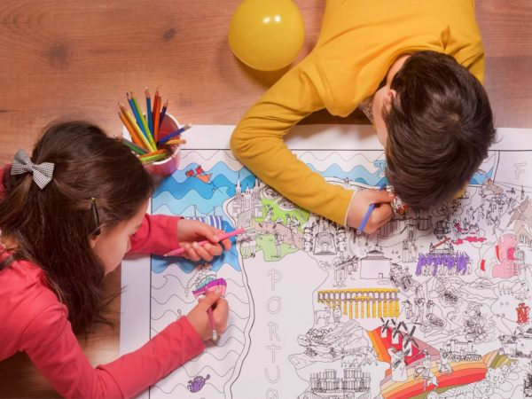 Detail of children painting on the floor the coloring map of Spain by Pinta y Pinto